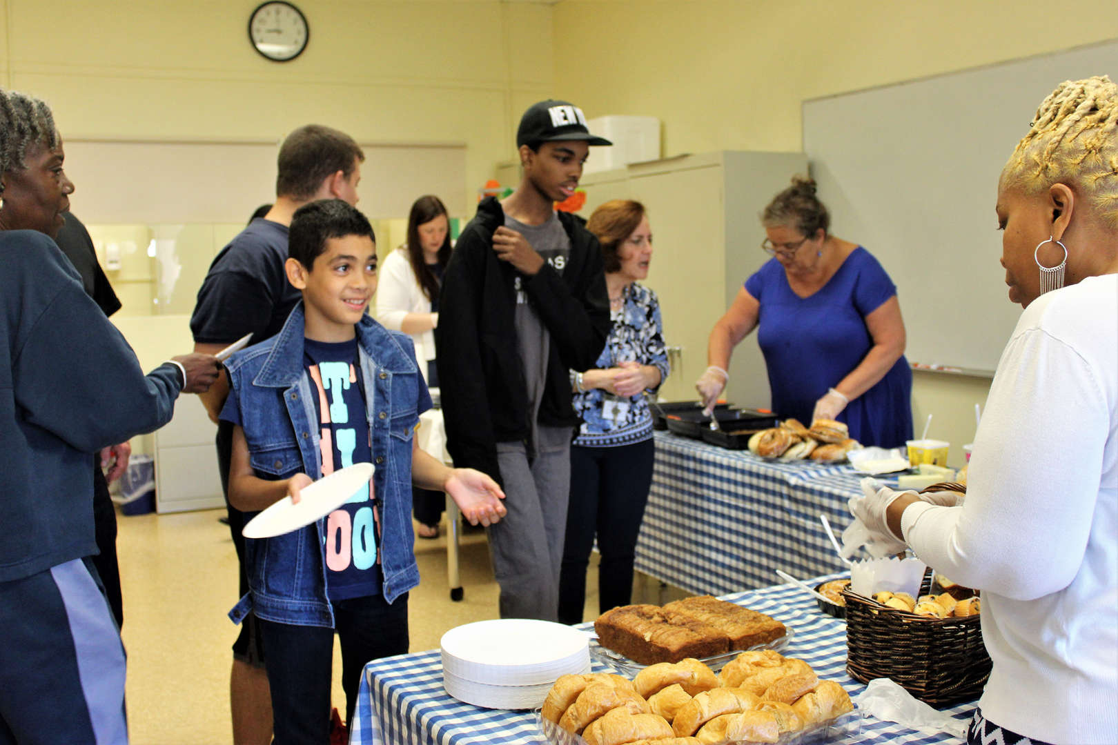 Staff members serve students at the Spirit Week breakfast.