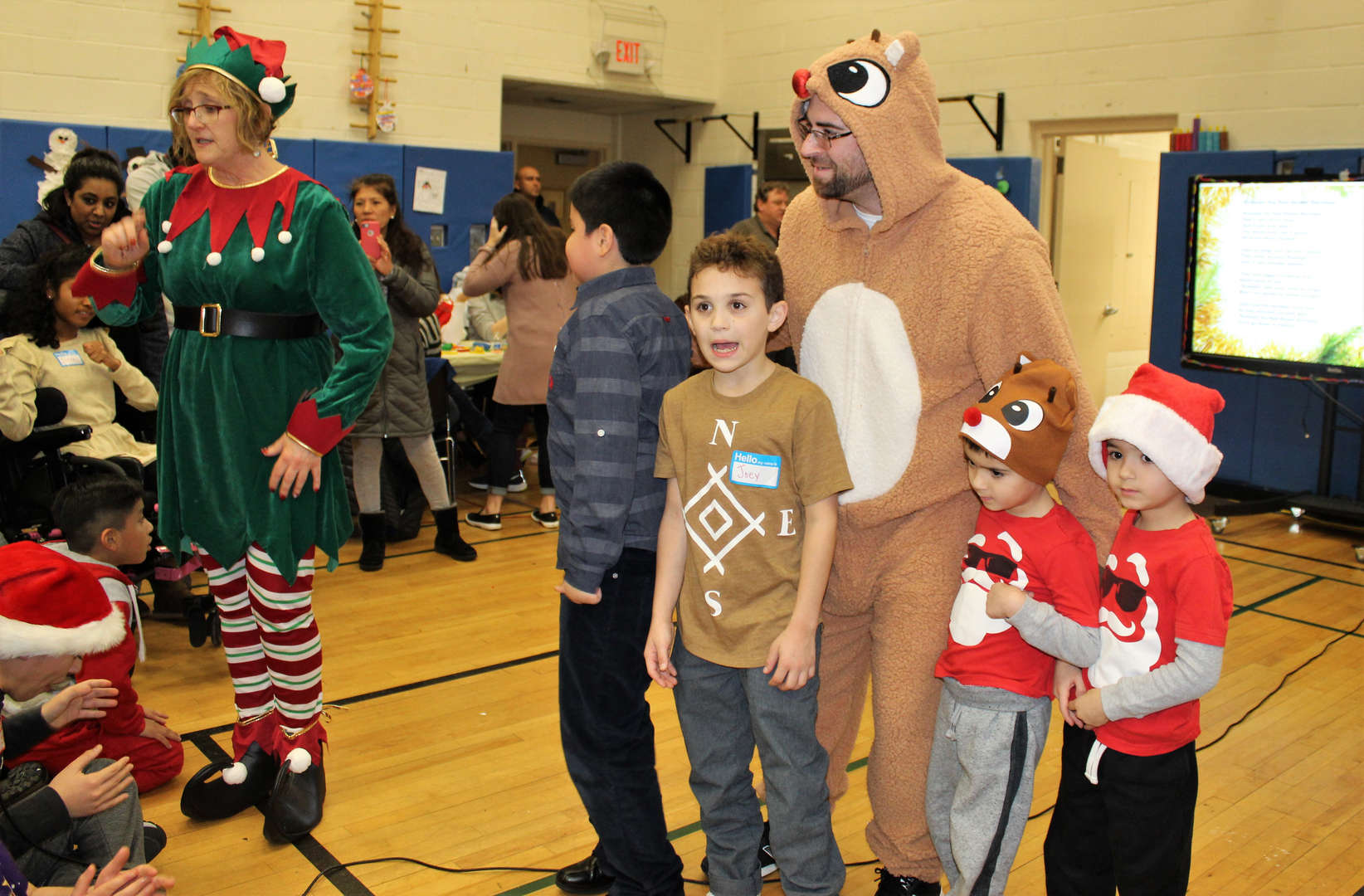 Children pose with one of Santa's elves and Rudolph the Red-Nosed Reindeer at a holiday party.