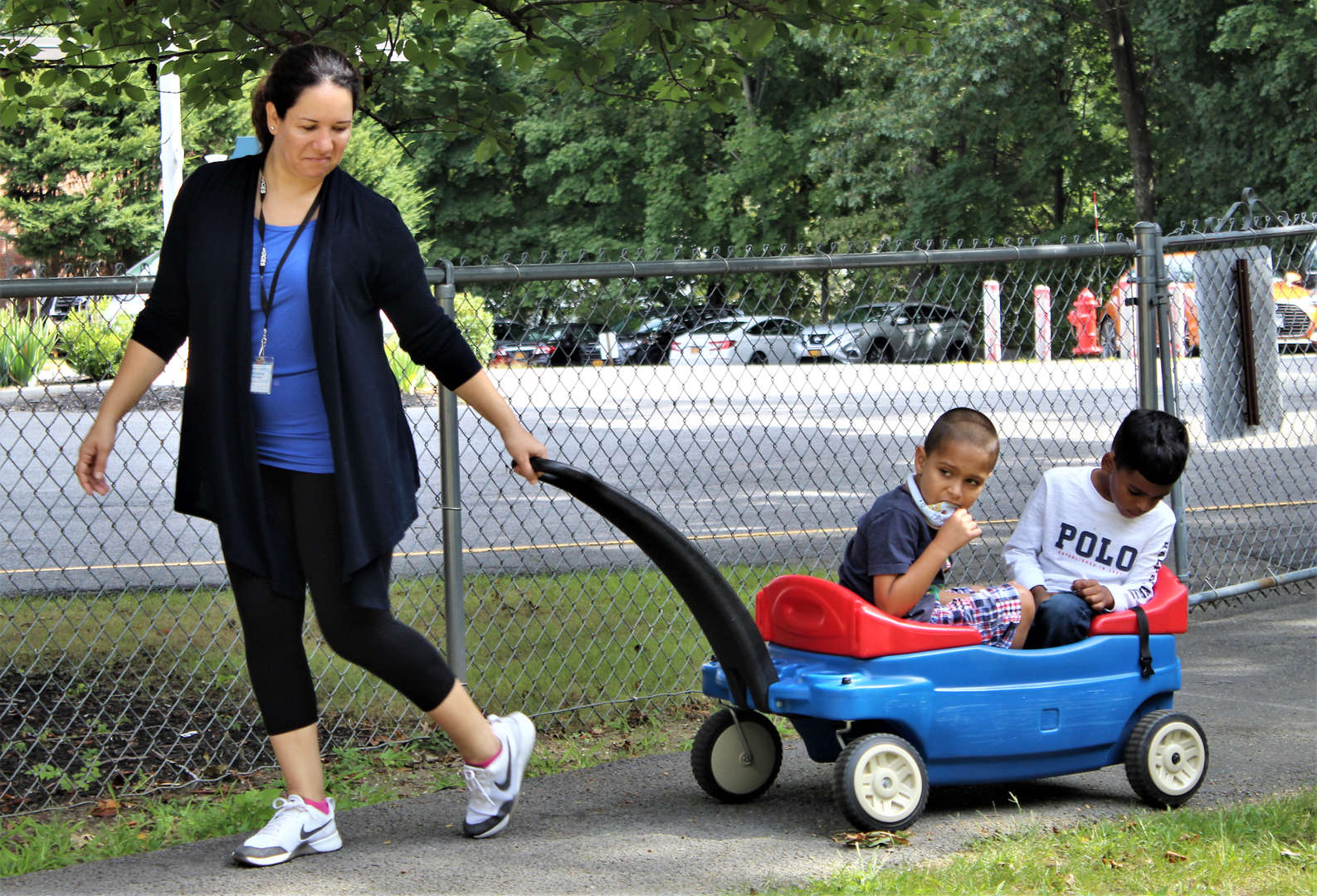 A staff member pulls two students in a wagon.