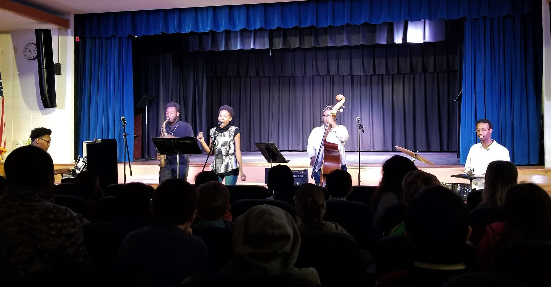 Five musicians perform for an audience of students and staff.
