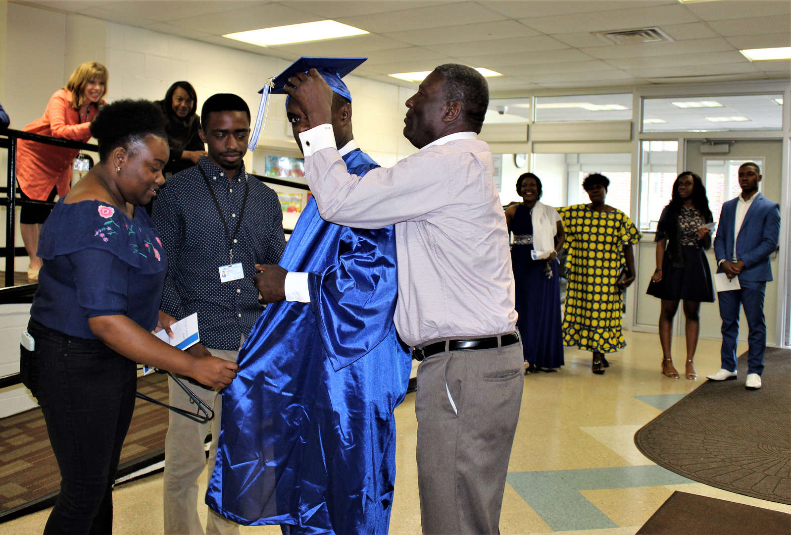 Staff members help a student get into his cap and gown on graduation day.