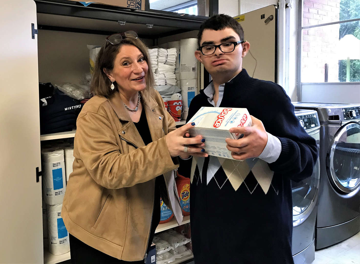 A male student and his mother pose in front of a supply cabinet in the laundry room.