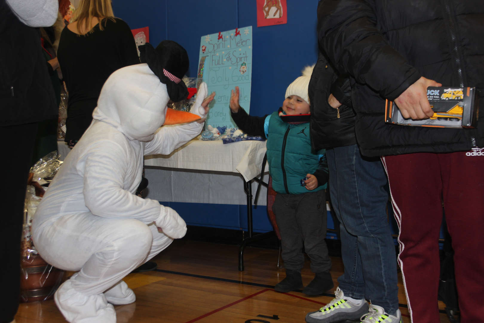 A staff member dressed as Frosty the Snowman gives a young boy a high-five.