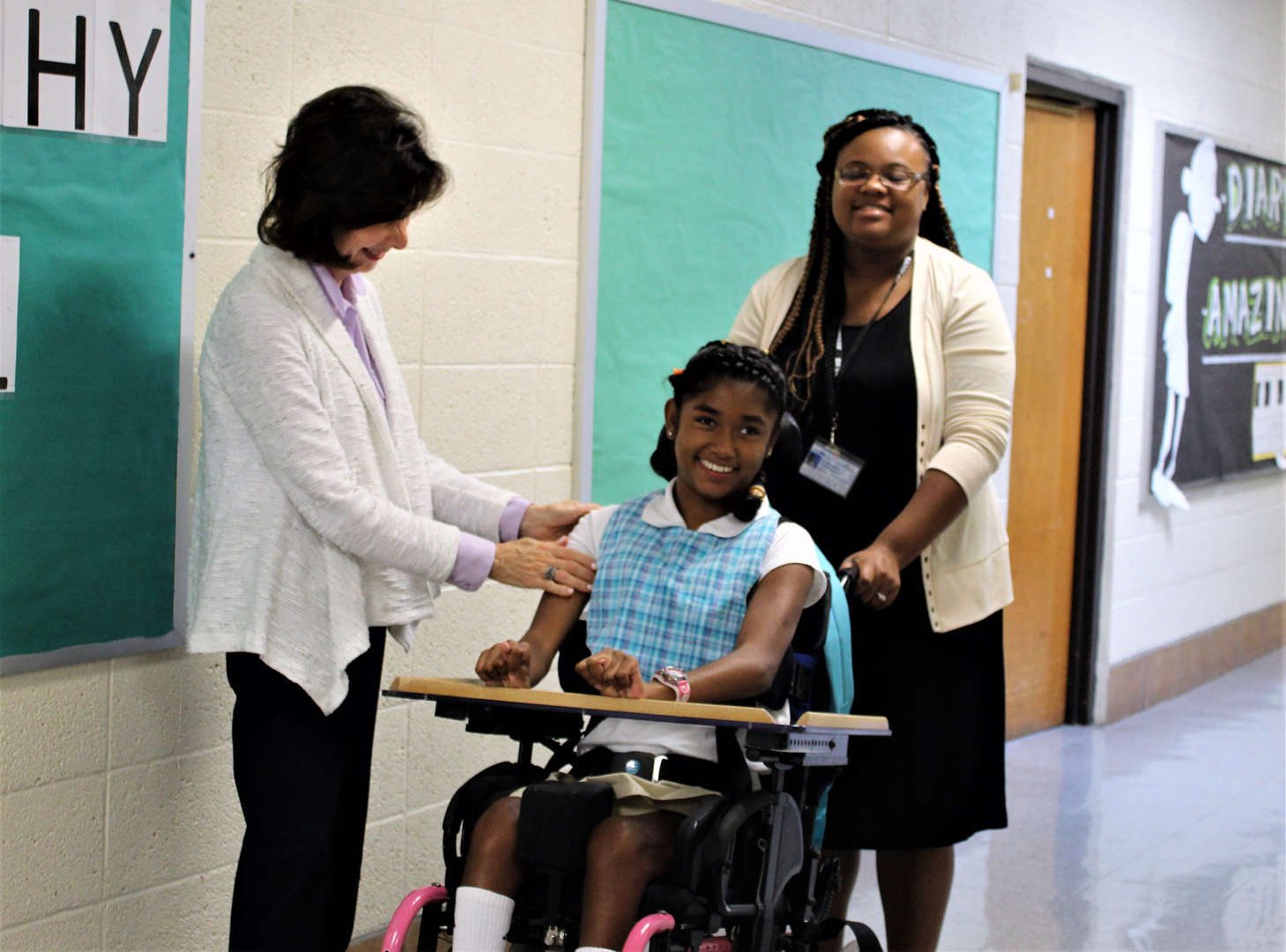 The principal greeting a wheelchair-bound student.