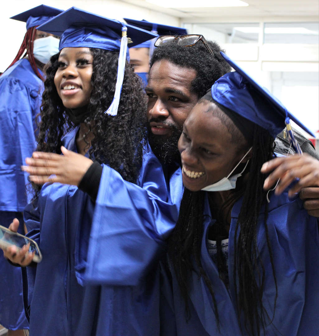 Graduates pose with school monitor Branden Dean before the ceremony.