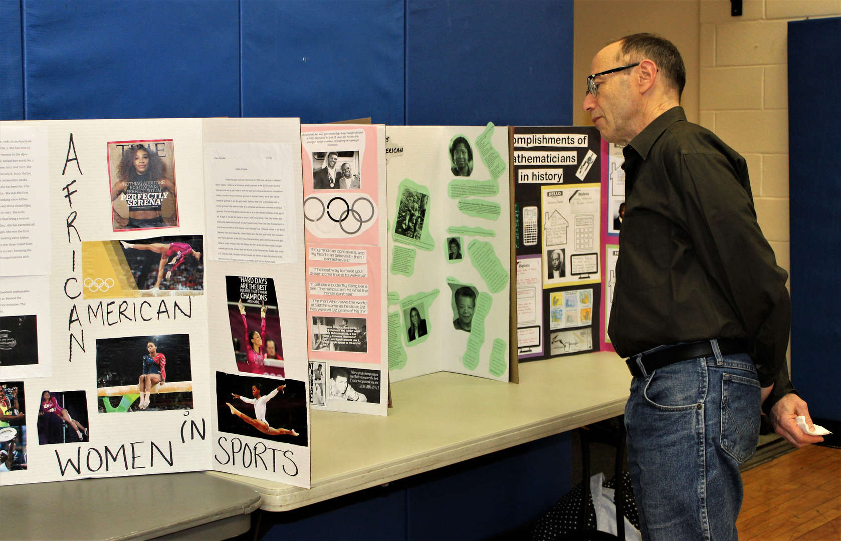 A male teacher looks at projects created on poster board.