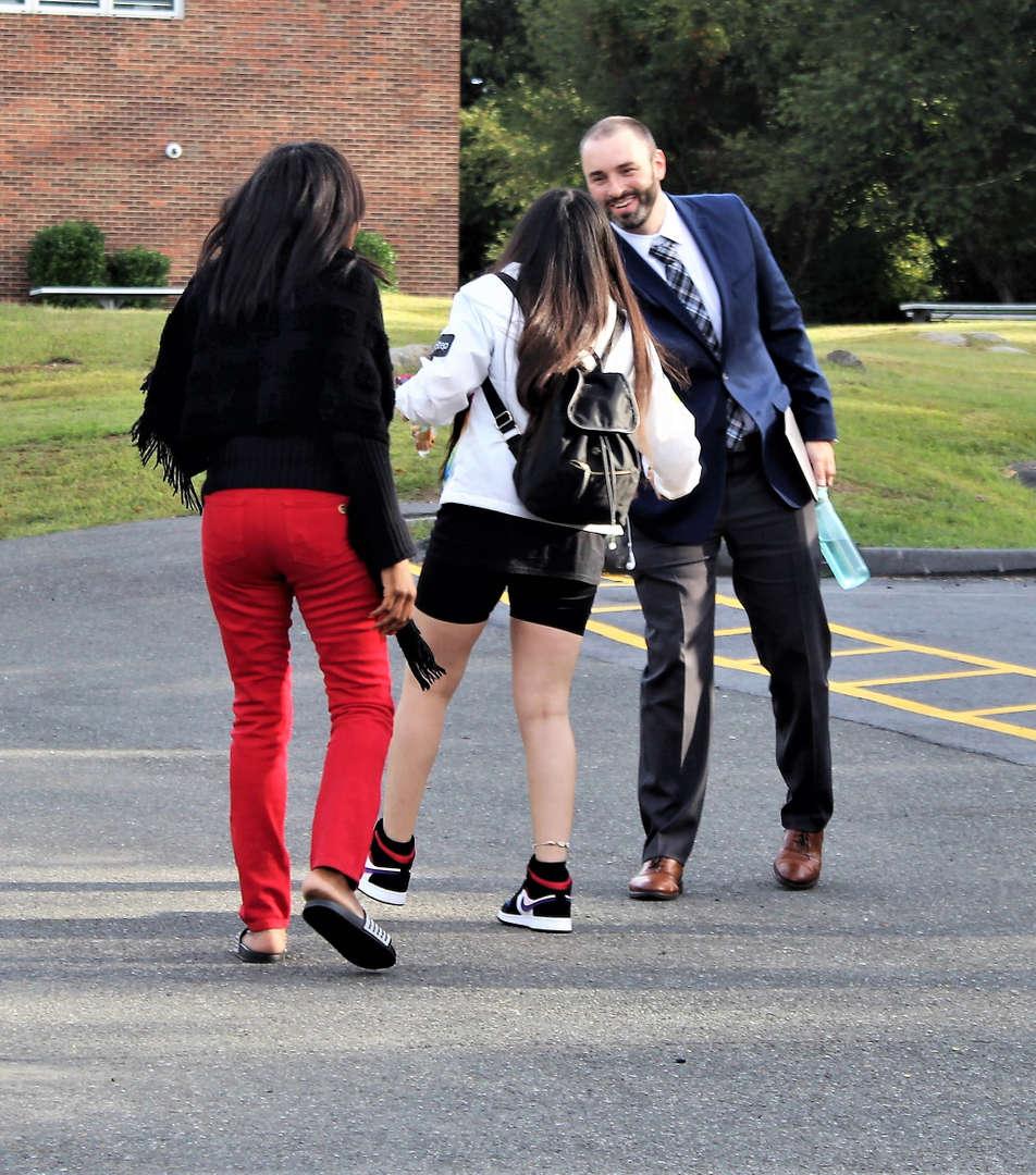 A school principal greeting a student.