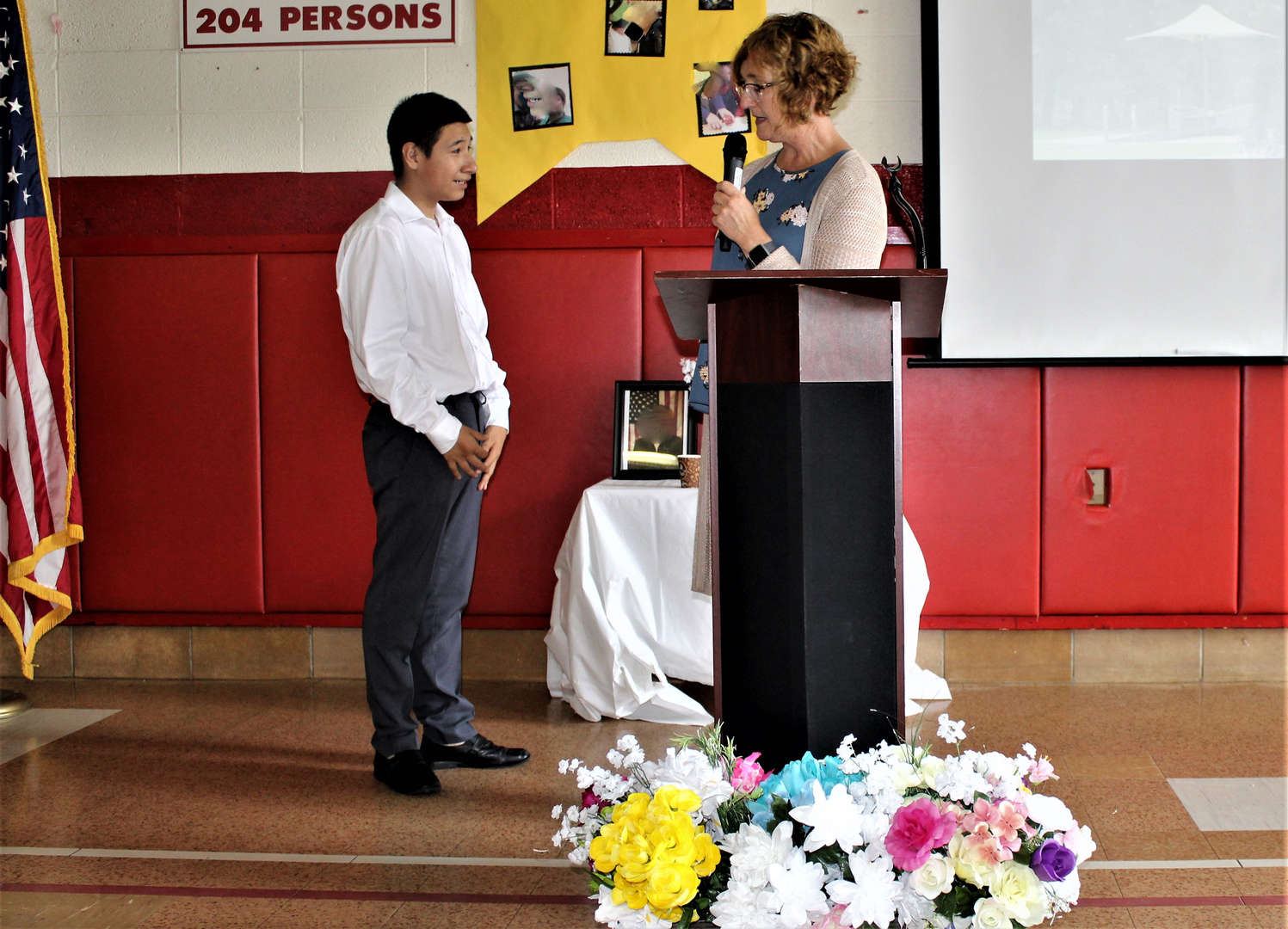 A teacher gives a moving-up certificate to a student.