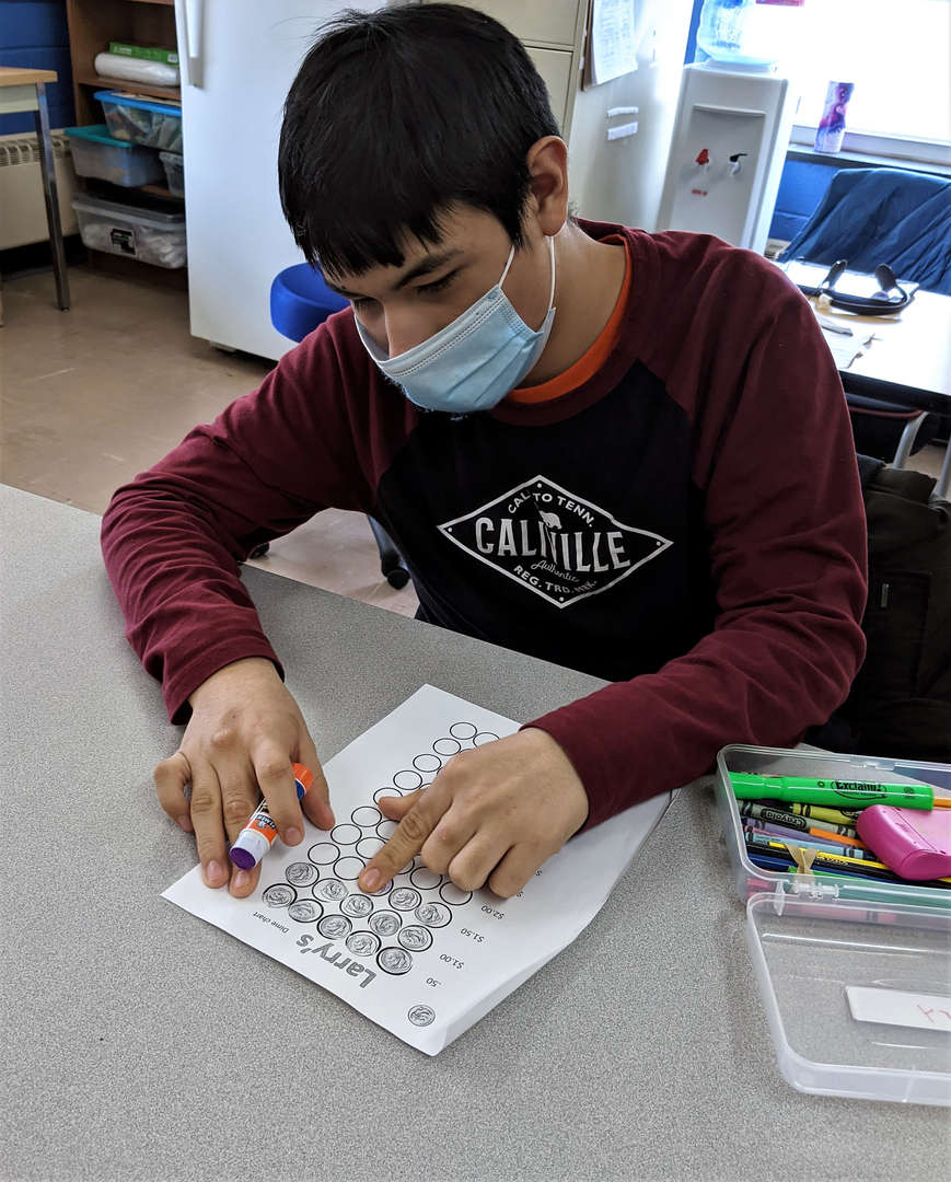 A male student counts how many dimes he has earned to spend at the School Store.