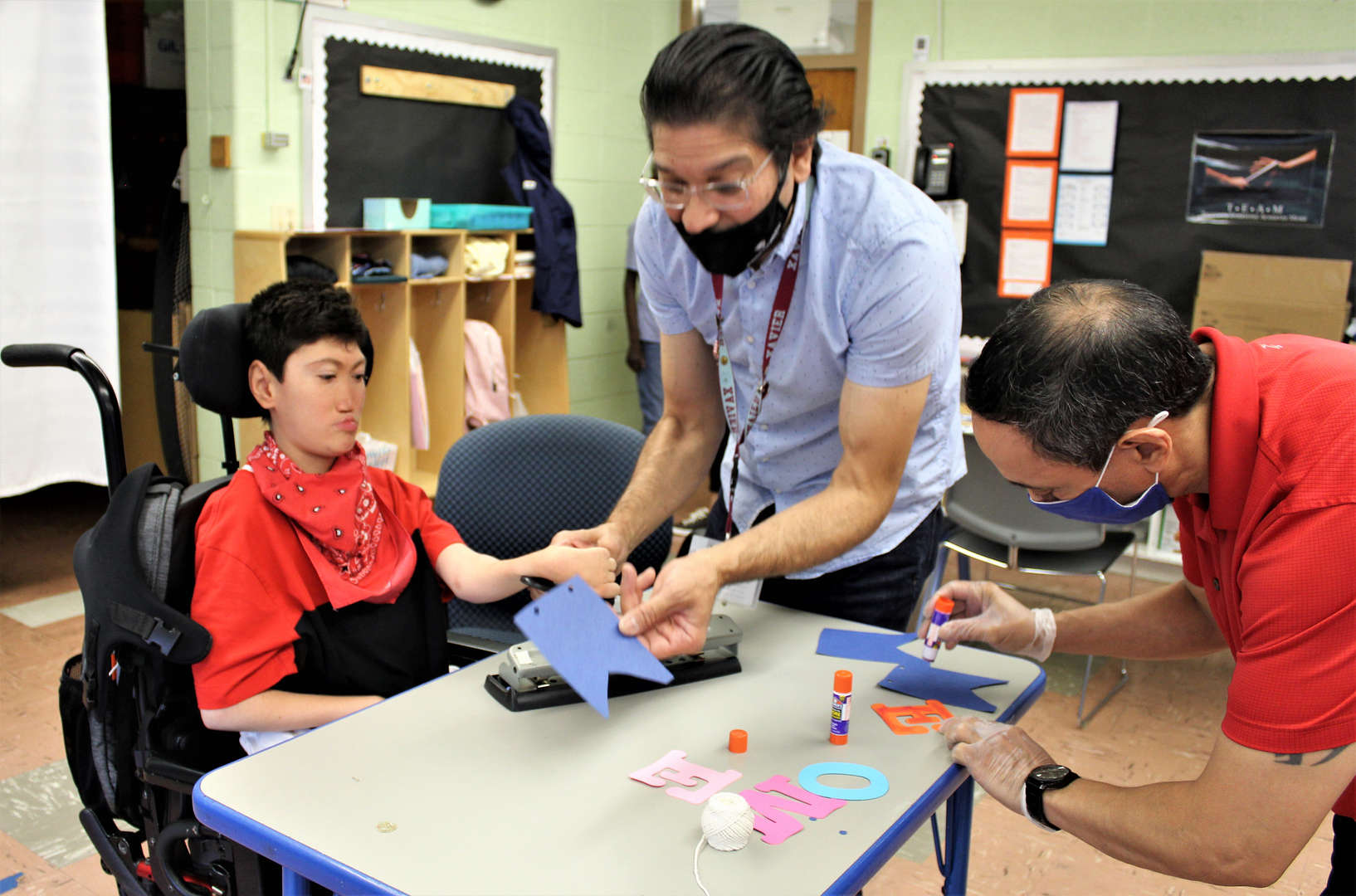 A teacher assists a male student using a feather-touch hole punch.