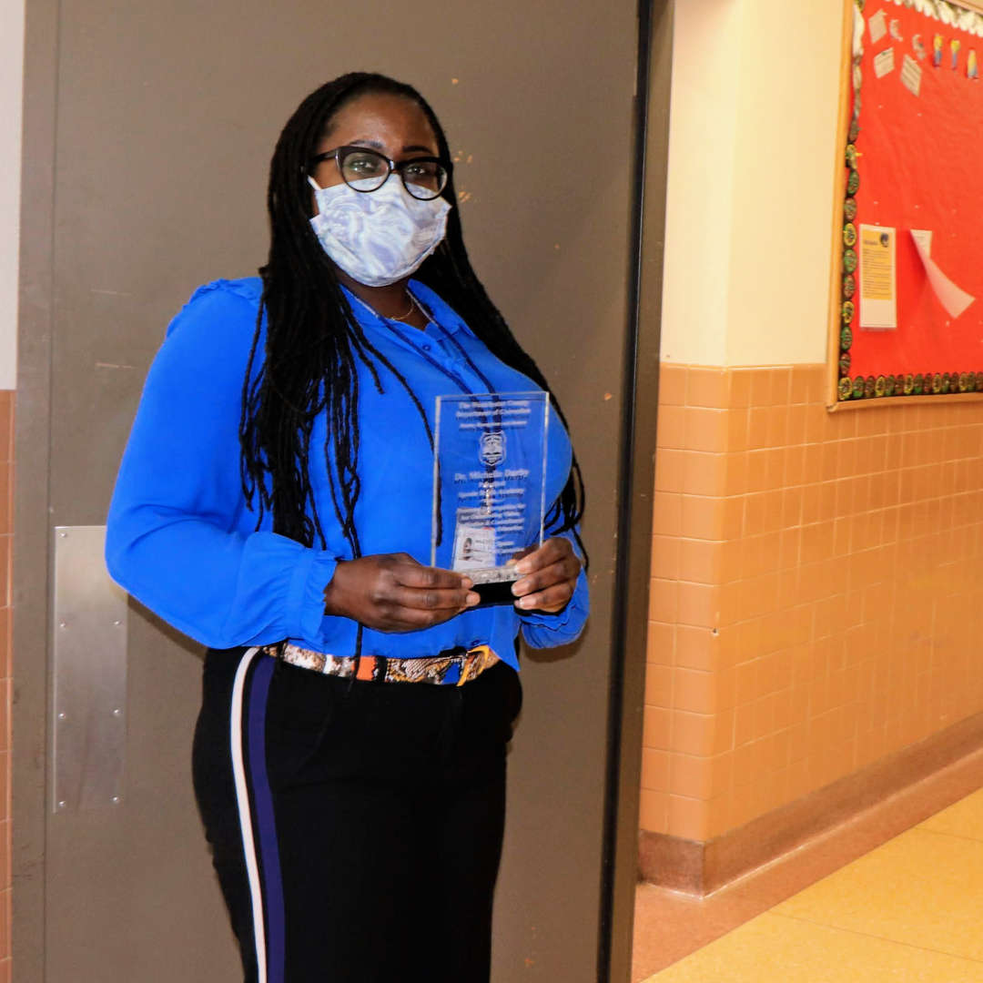 Dr. Michele Darby holding her award.