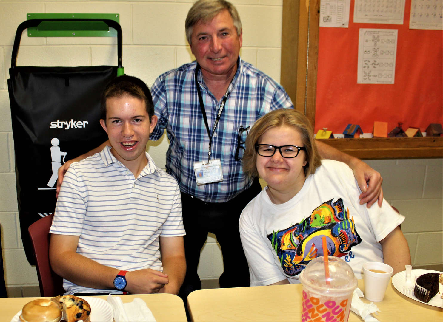 A teacher poses with two students at the Spirit Week breakfast.