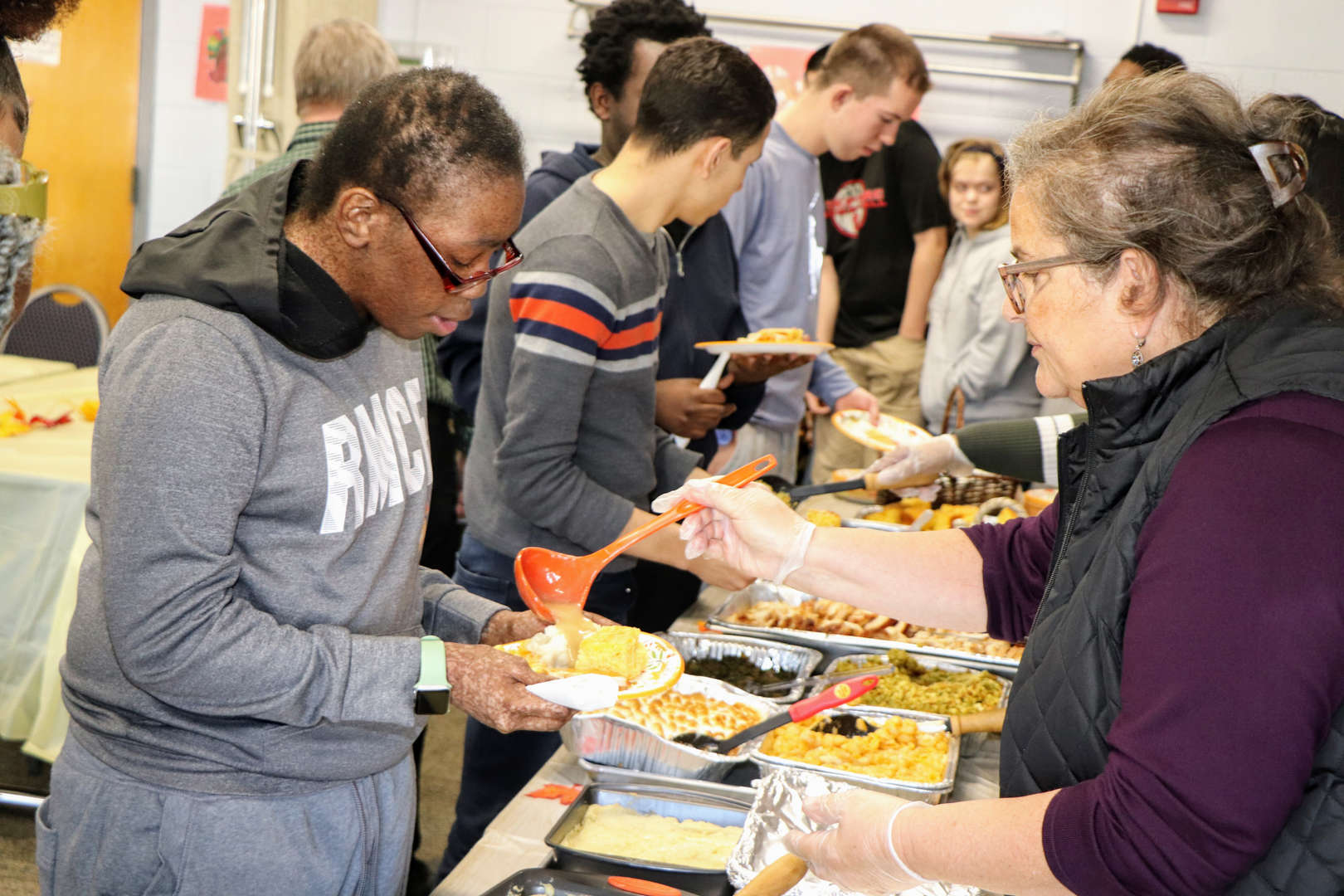 staff and faculty served by colleagues at Thanksgiving luncheon