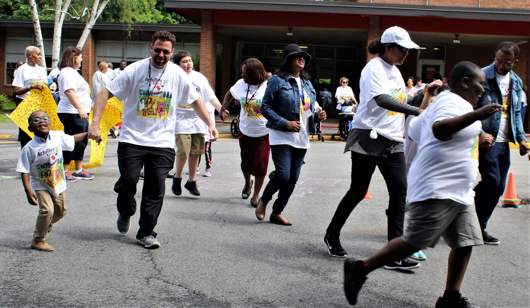 Staff members hold students' hands as they run the last lap.