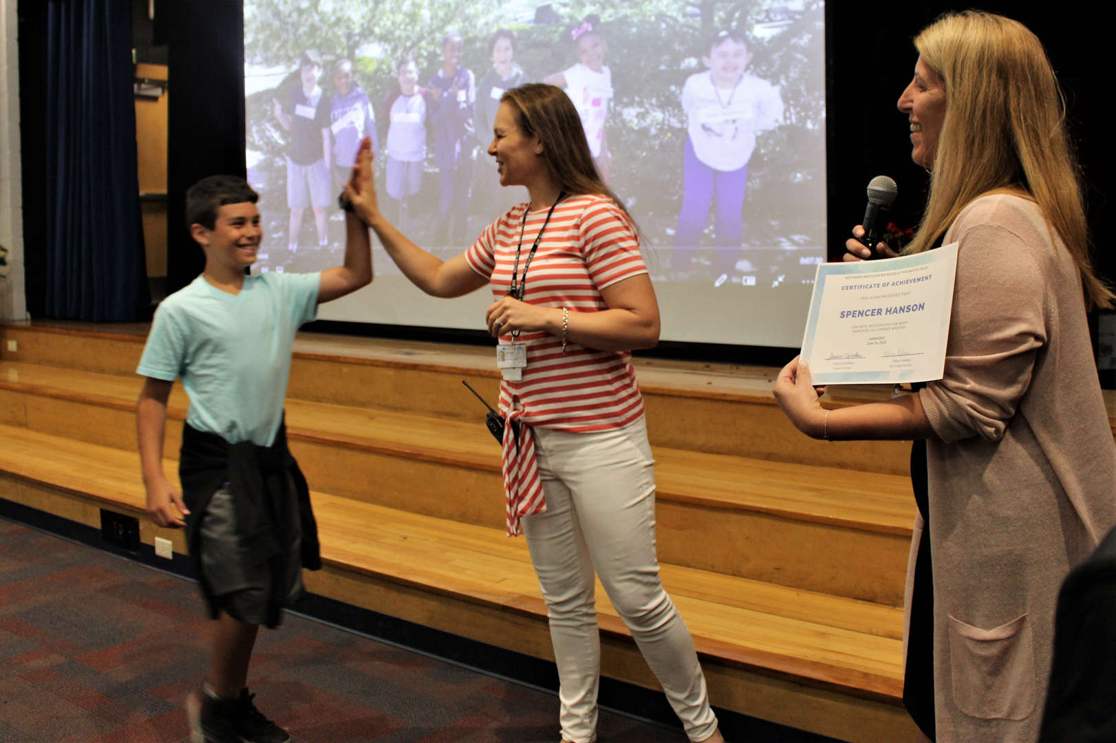 A teacher gives a student a high-five during an awards and moving-up ceremony.