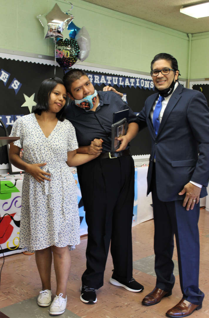 One female and one male graduate pose with their teacher.