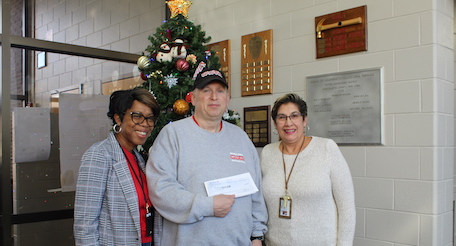 administrators present check to Toys for Tots organizer