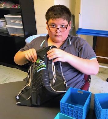 students stuffs backpack as part of summer vocational work program