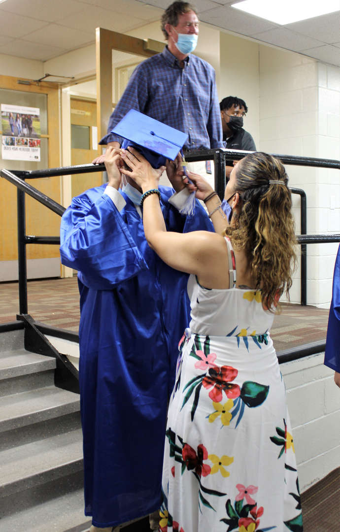 Teaching assistant Edith Rivera helps a graduate get ready for the ceremony.