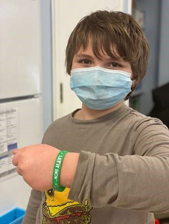 "A male student displays a ""Let it snow"" bracelet."