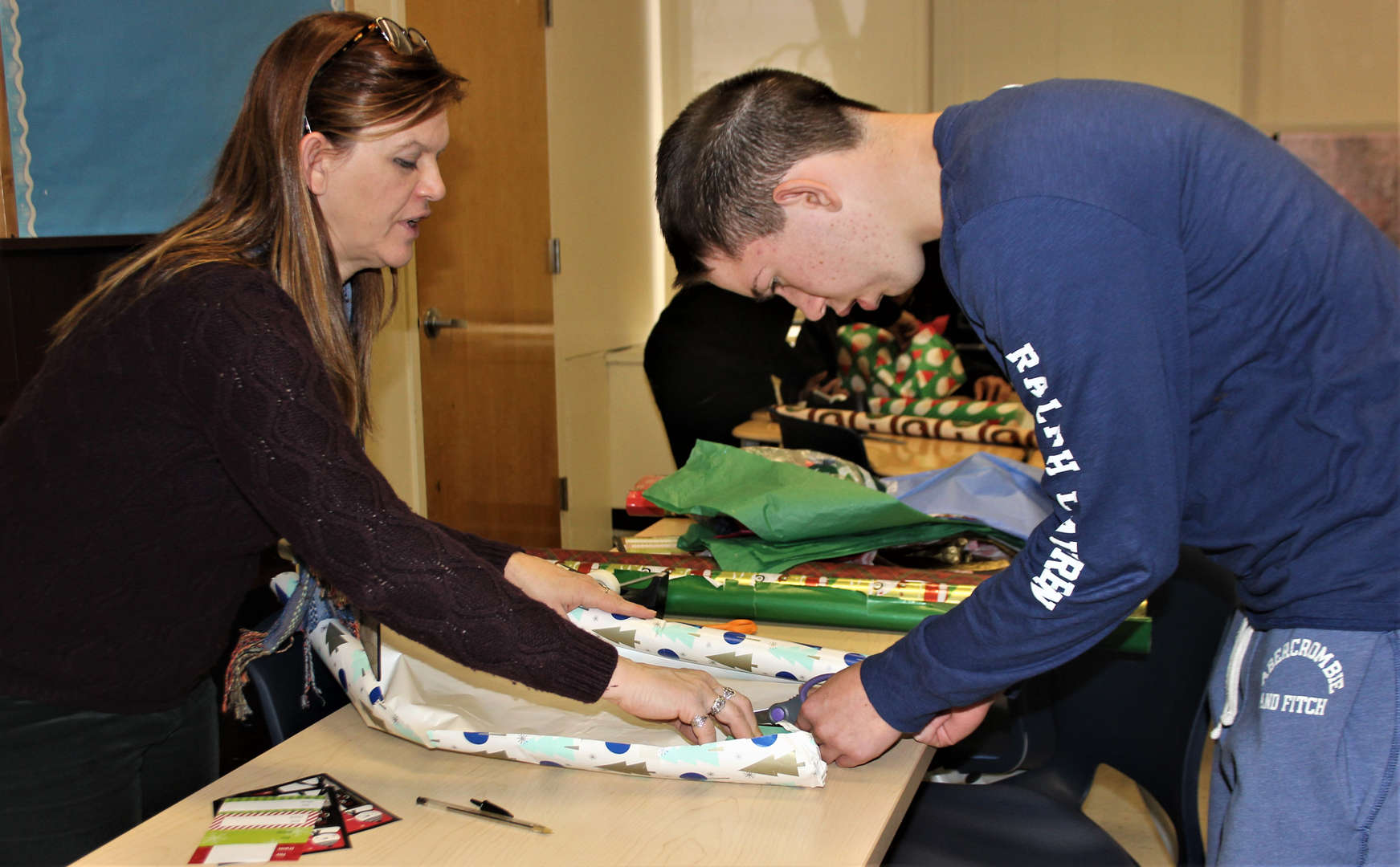 Photo of a student getting help wrapping his gift.
