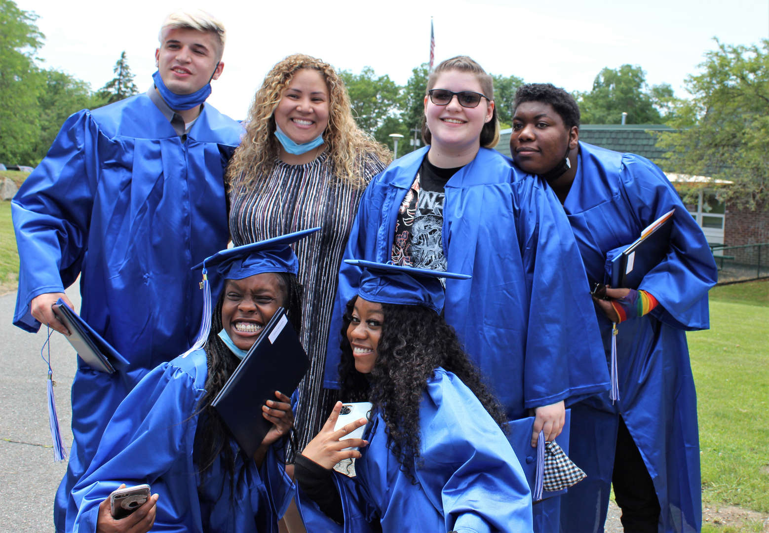 School counselor Cristina Tompkins poses for a photo with students after the graduation ceremony.