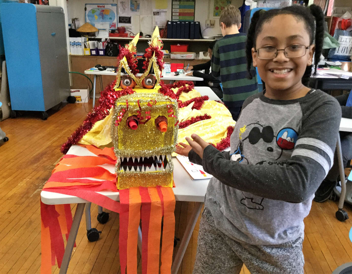 A male student shows off the dragon costume his class created.
