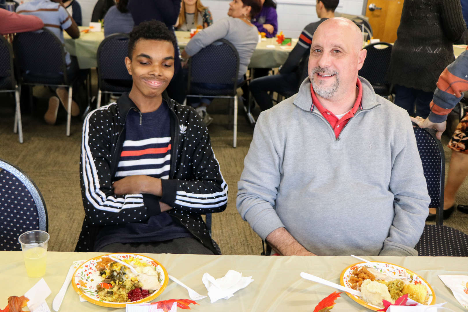 teacher and student seated for Thanksgiving luncheon