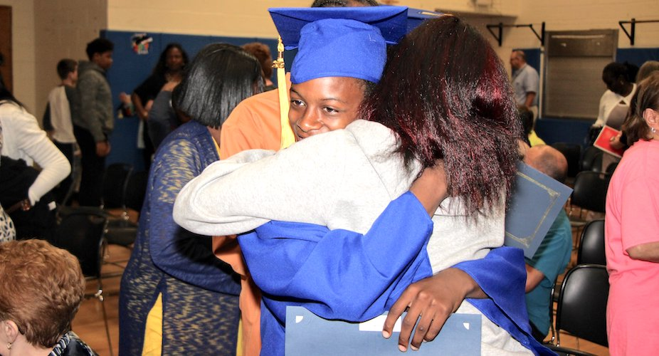 Graduate hugging family member after ceremony