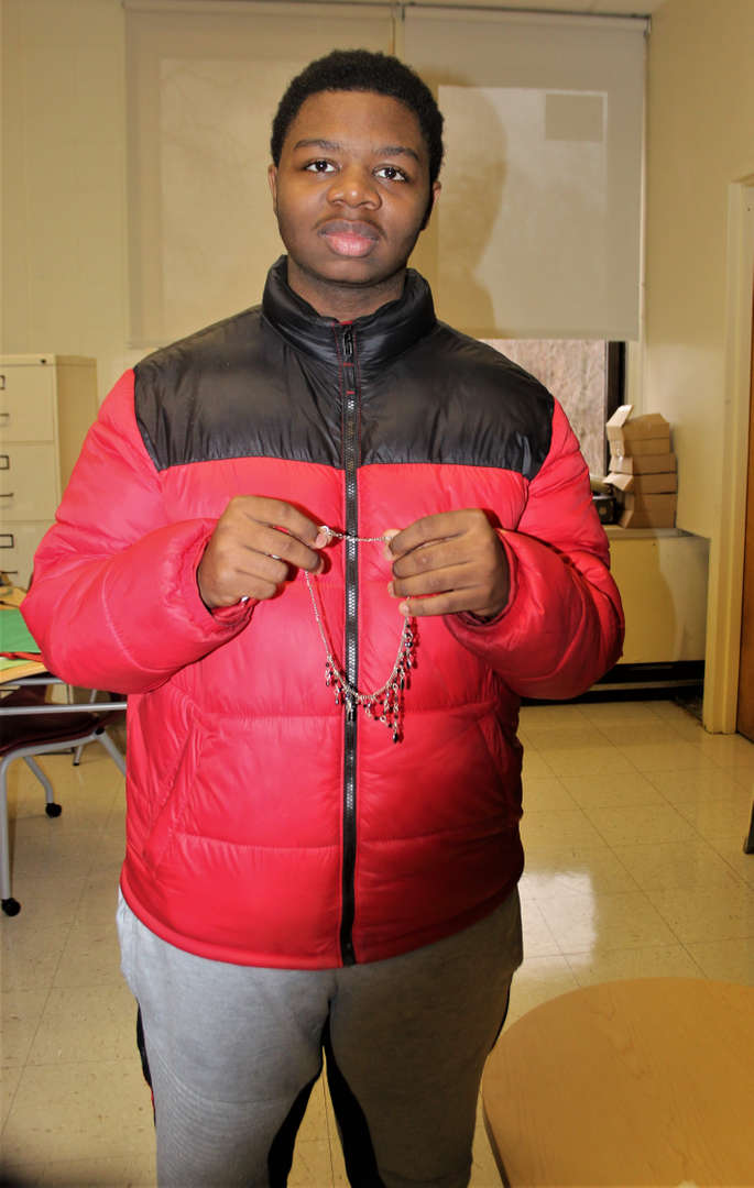 Photo of a student holding up a necklace he chose as a gift for his mother.