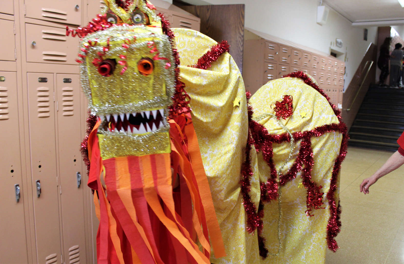 Three students wear the dragon costume the class created for the Lunar New Year.