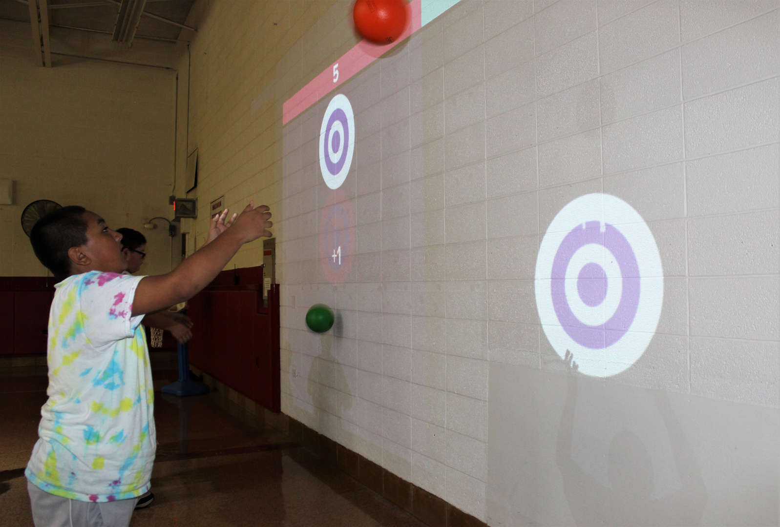 A male student plays a Lu interactive playground game at Tappan Hill School.