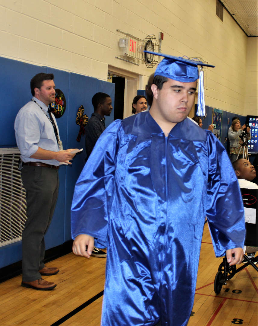 A student graduate walks into the gymnasium.