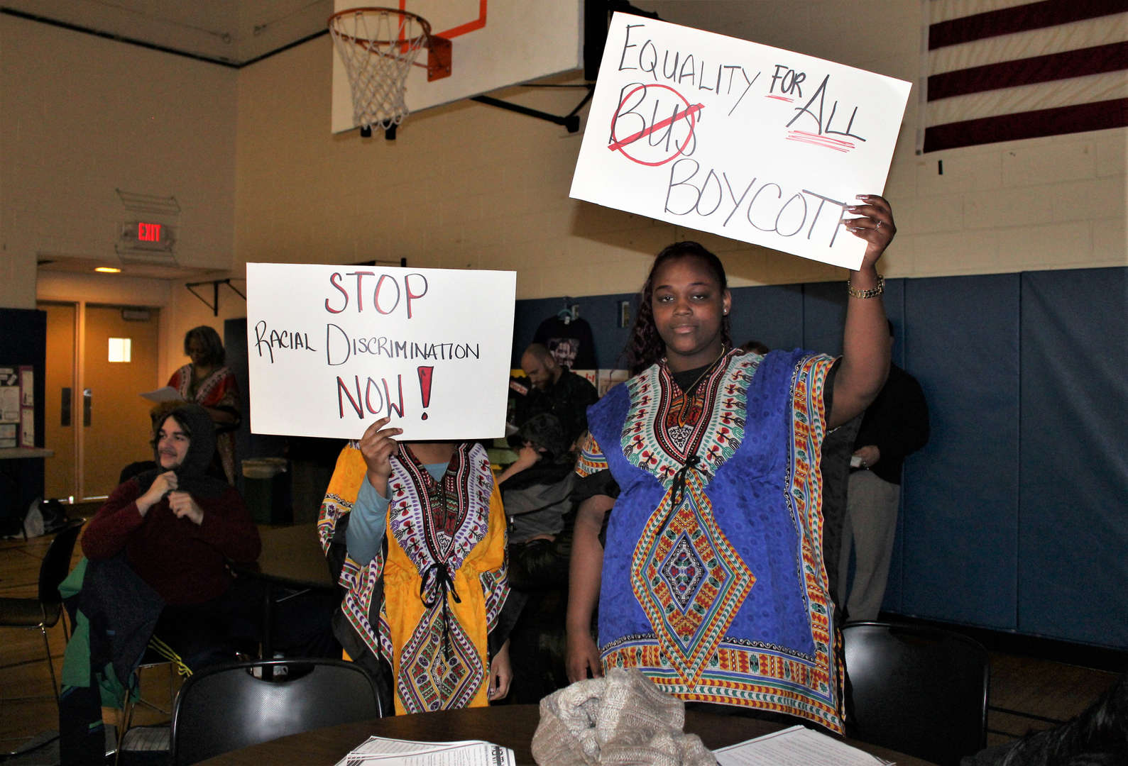 Two female students hold up protest signs.