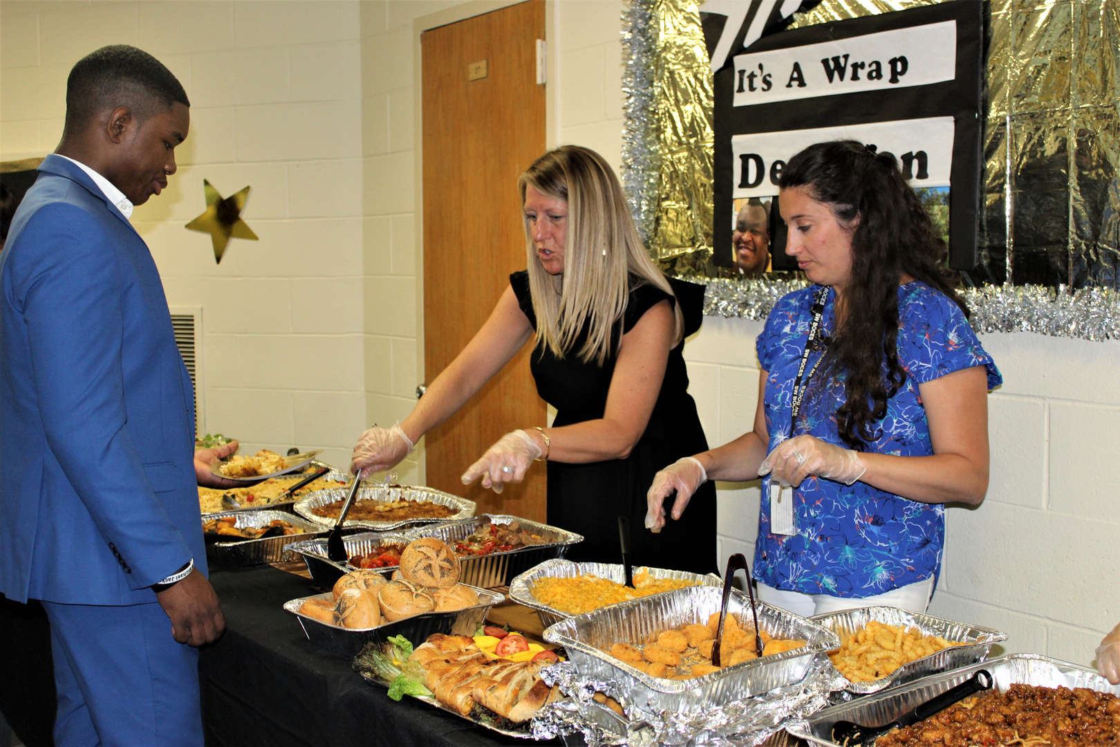Staff members serve food they made.