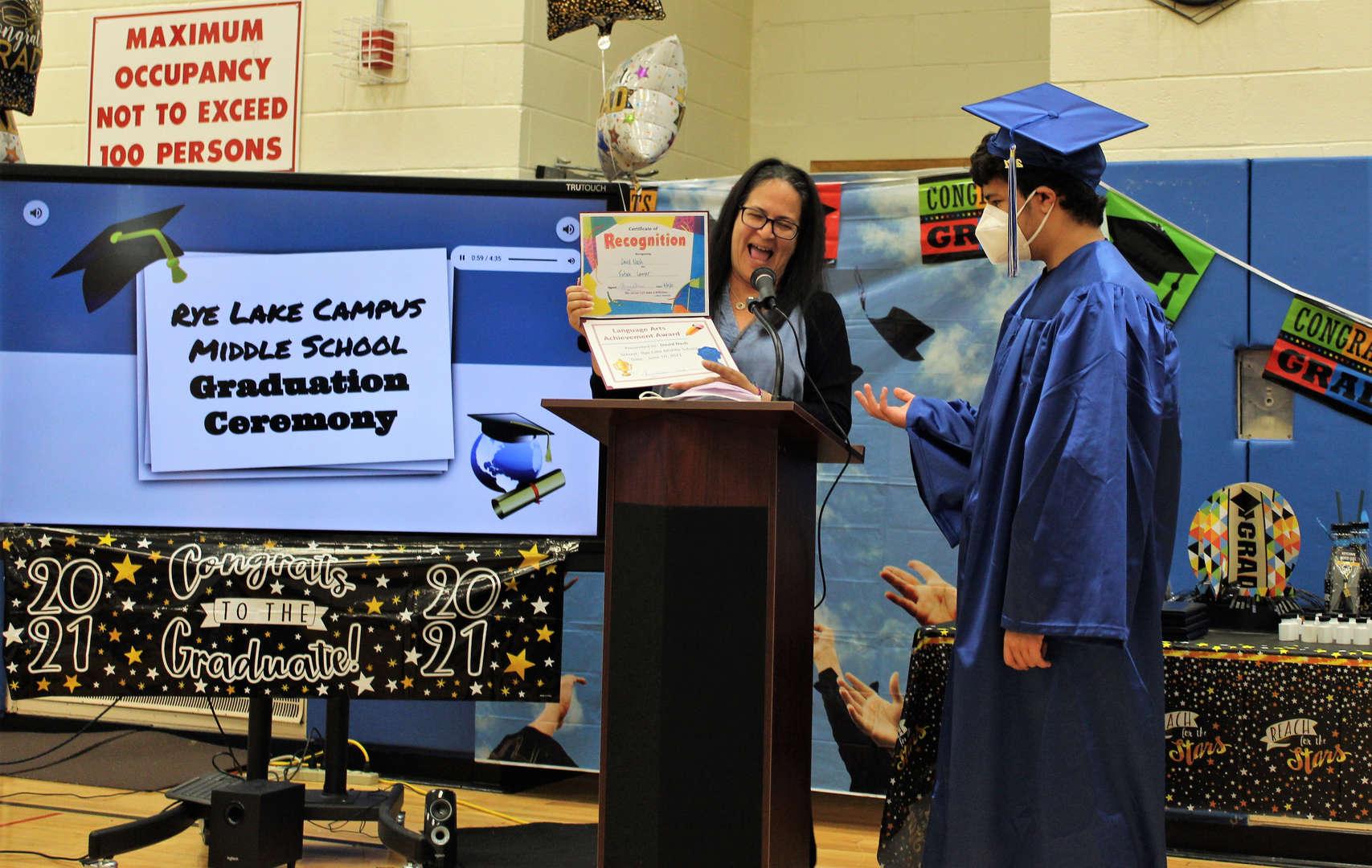 Graduate David Nash accepts an award from teacher Tiziana DeMasi.