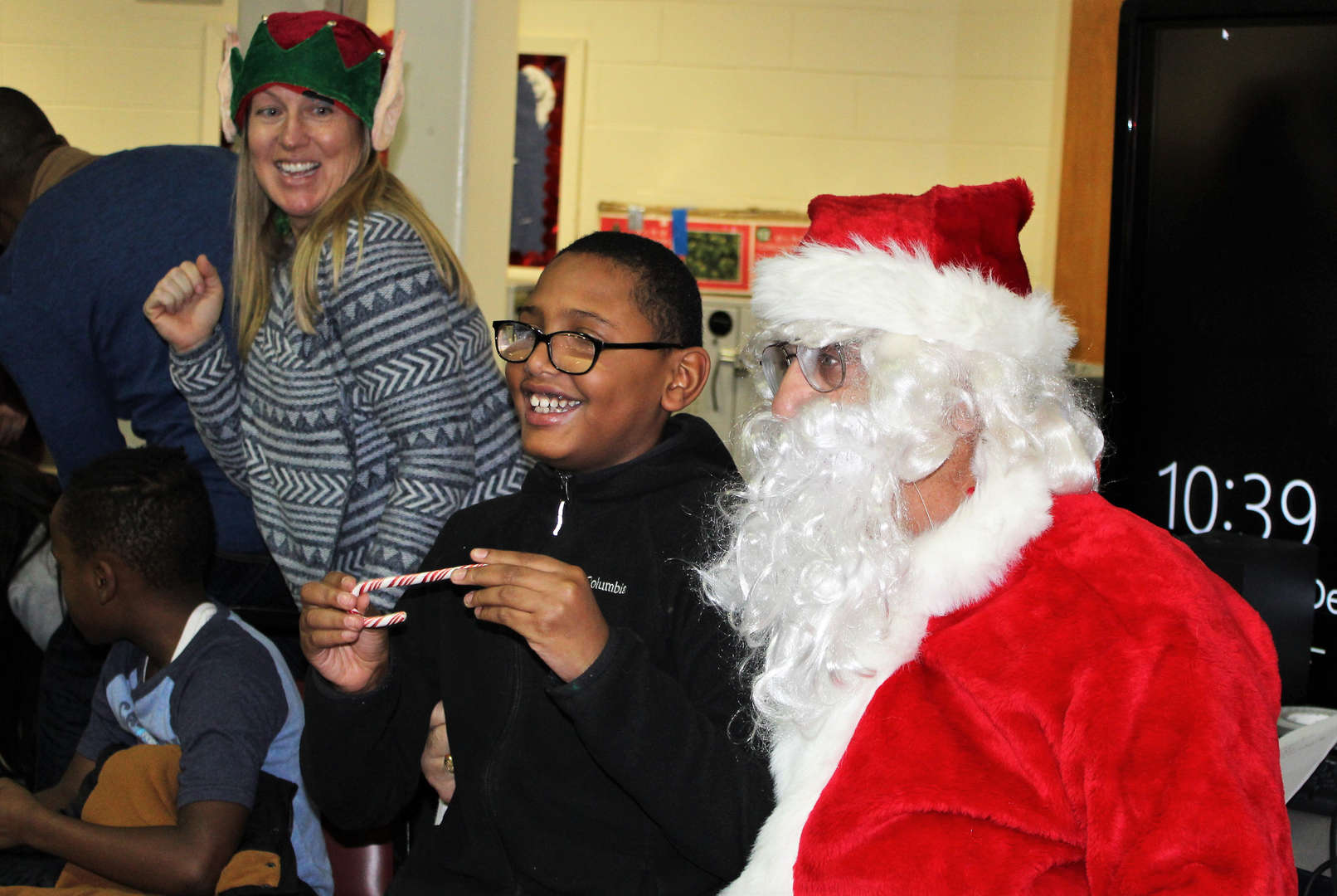 A male student received a candy cane from Santa Claus during the holiday singalong at the Decagon