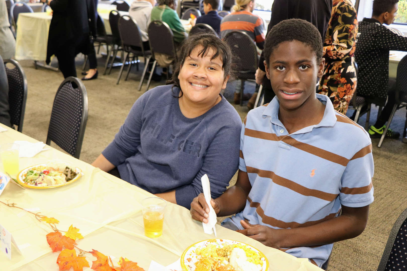 Two students smile during Thanksgiving luncheon