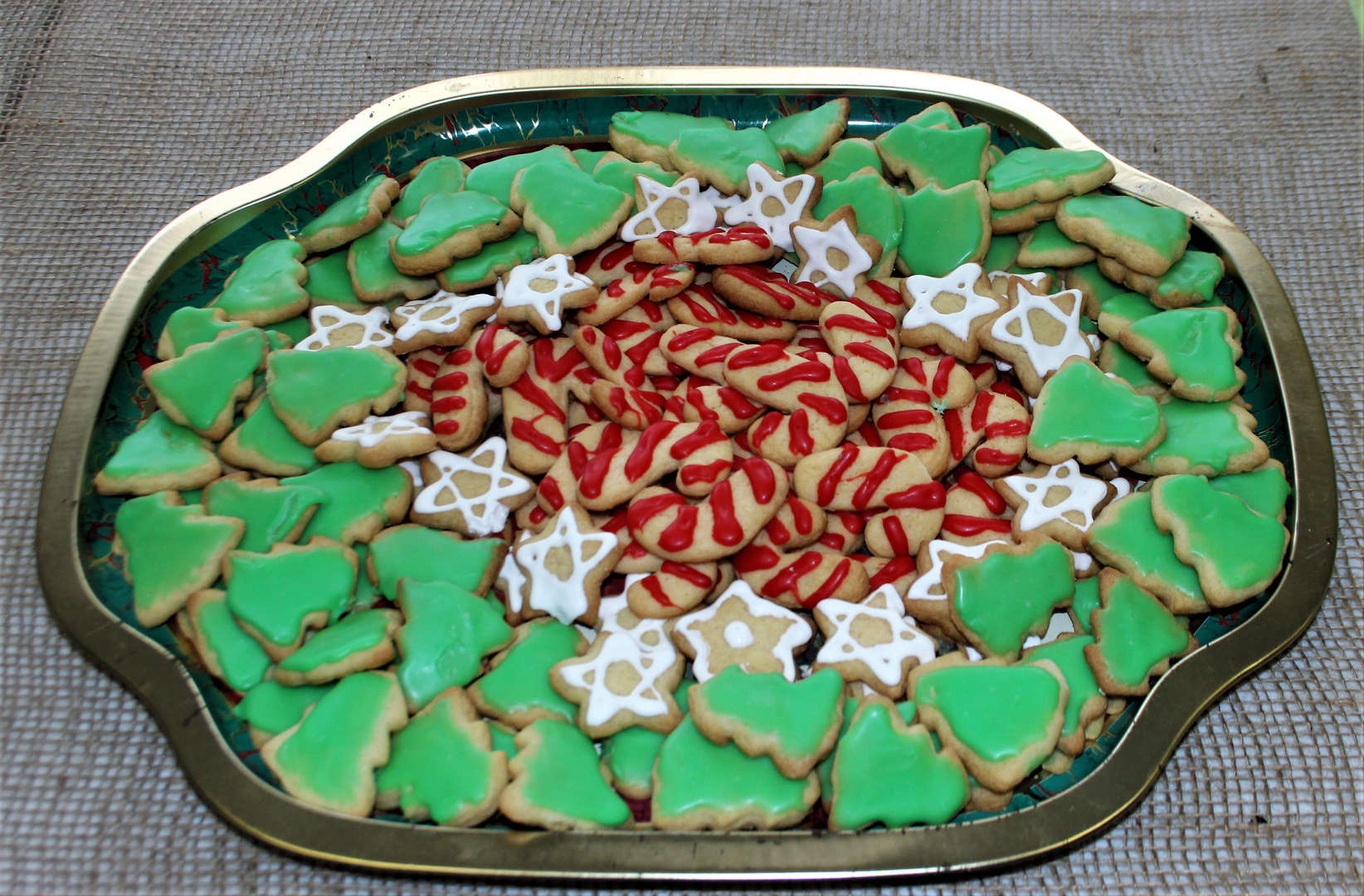 Photo of a platter of sugar cookies in the shape of stars, trees and candy canes.