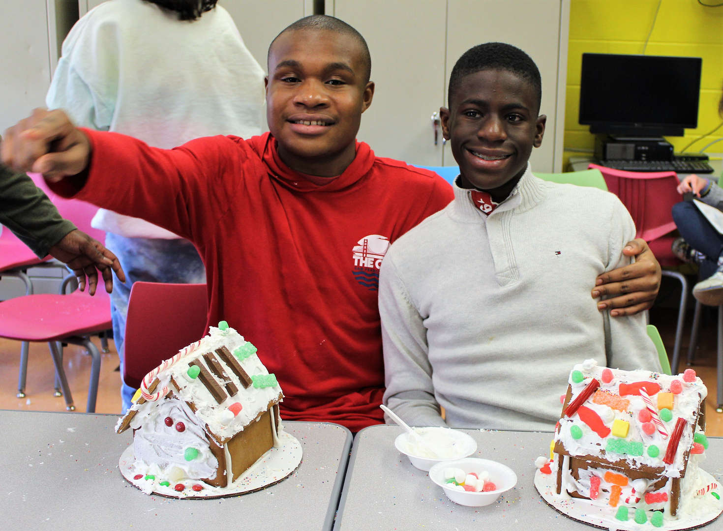 Two male students show off their decorated gingerbread houses.