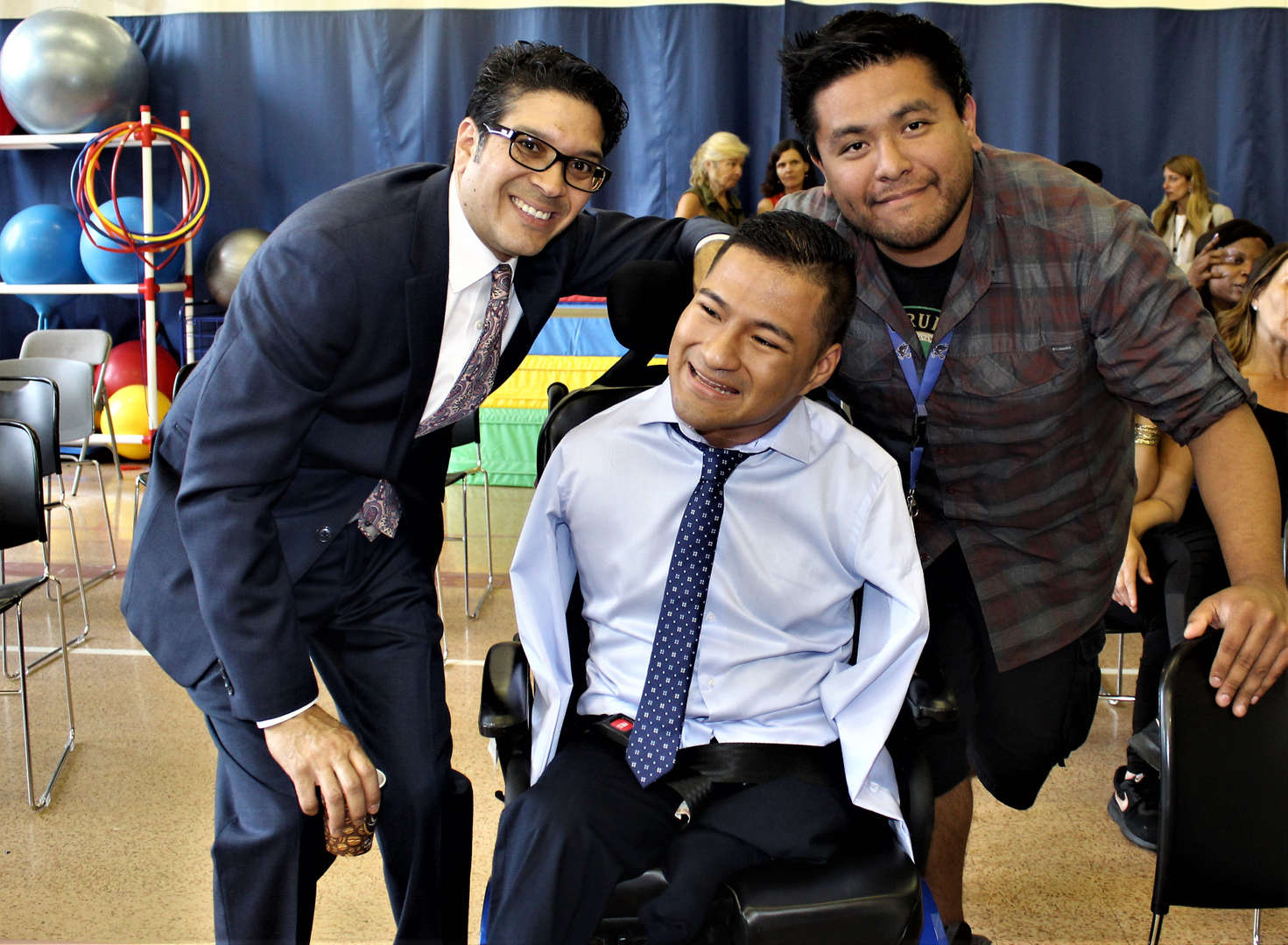 School staff pose with graduate Steven Arellano for a photo.