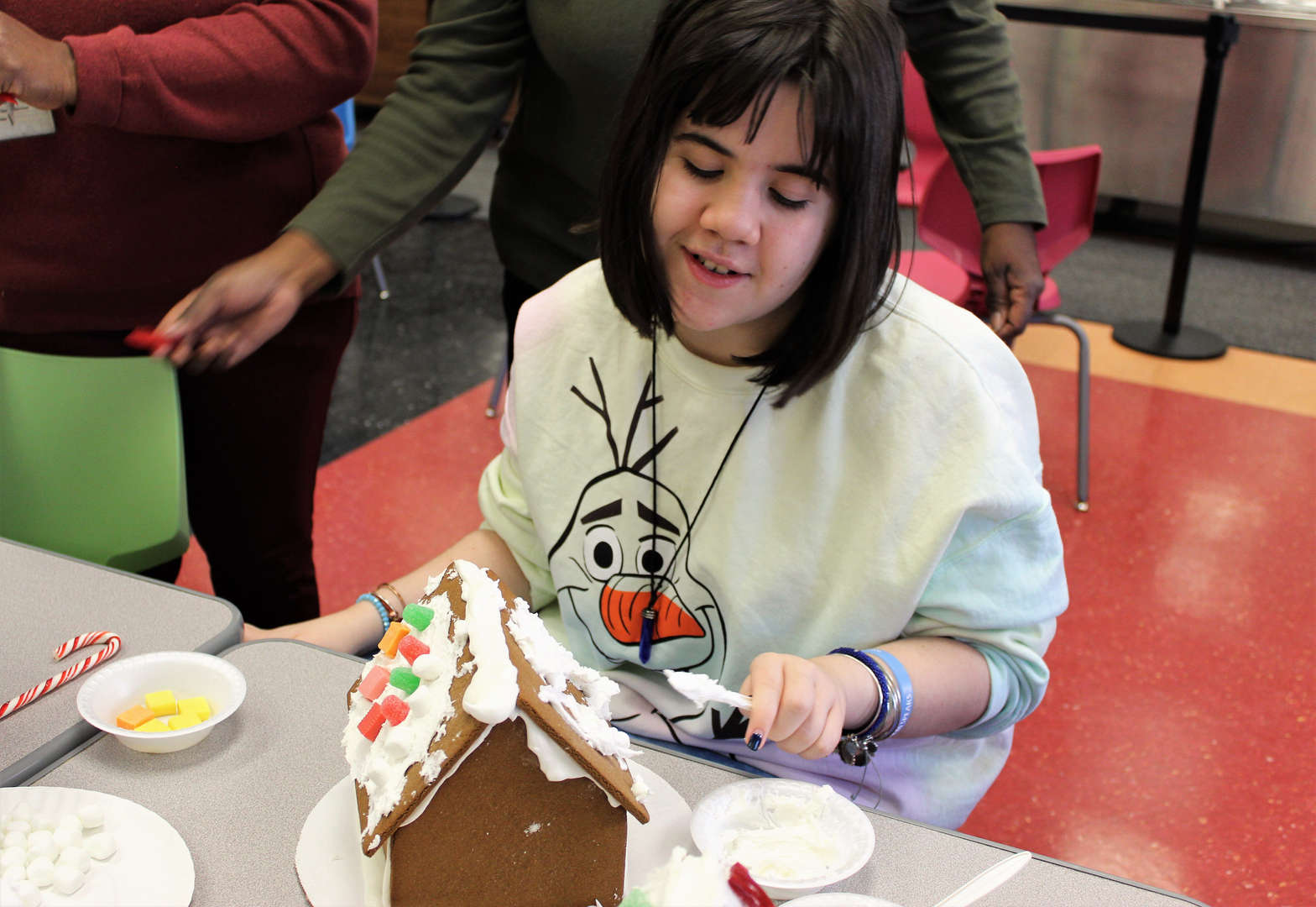 A female student decorates her gingerbread house with candy.