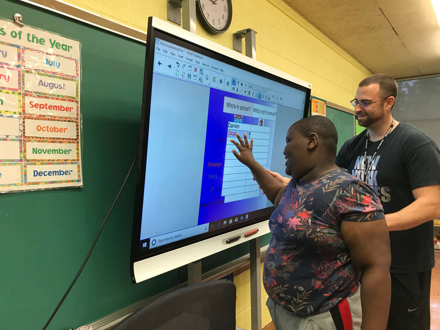 A student uses the SMART Board to sign in for the day.