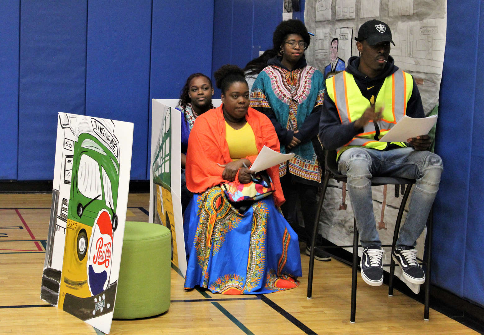 Three students and two staff members pretend to ride a bus during a Black History Month skit.