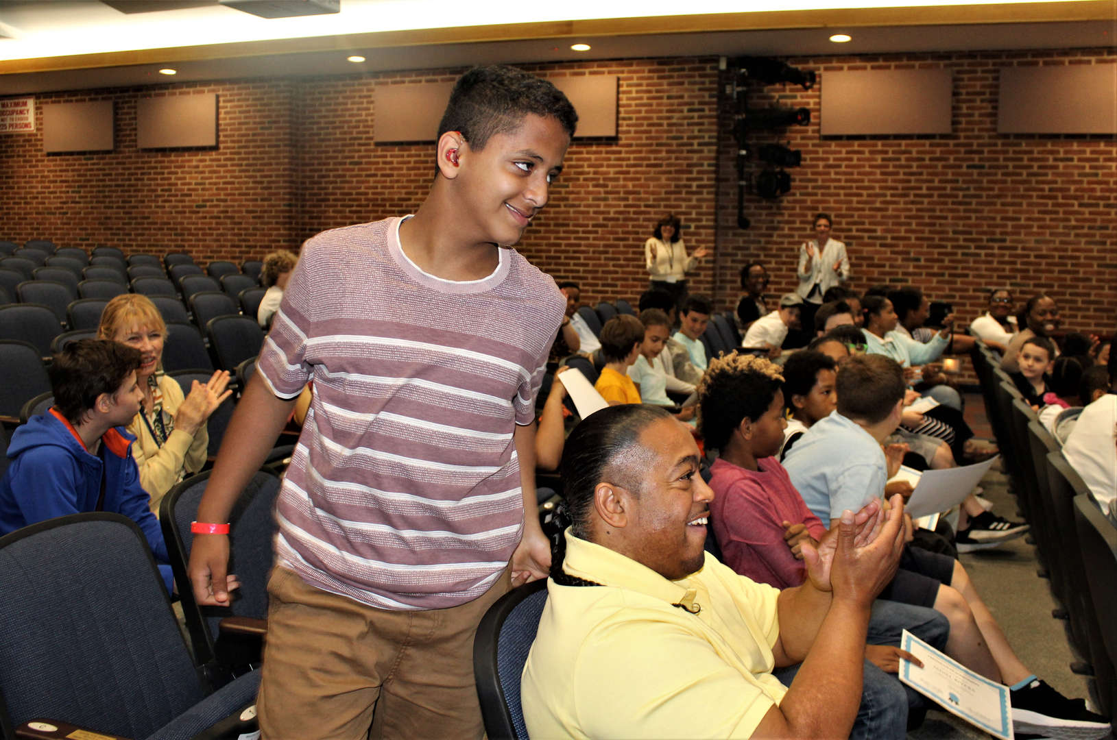A student gets up from his seat to receive an award at the front of the auditorium.