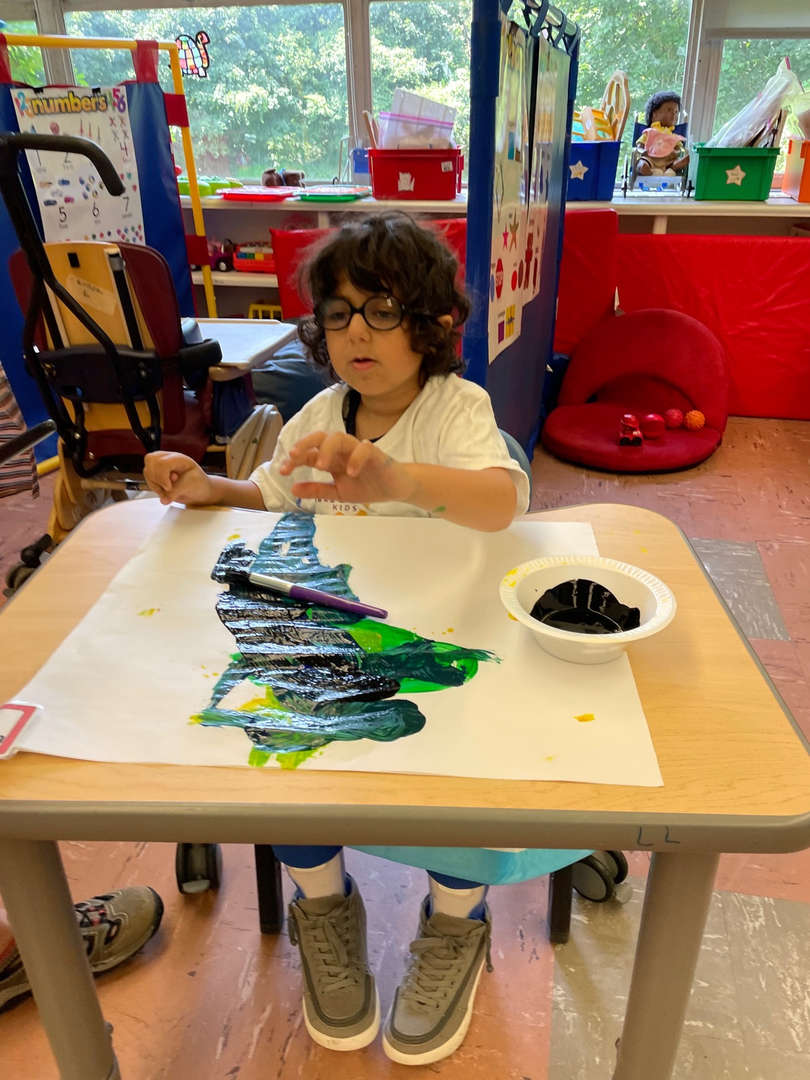 student works on artwork in style of Jackson Pollock