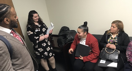 aide stands as student, seated, tells her story