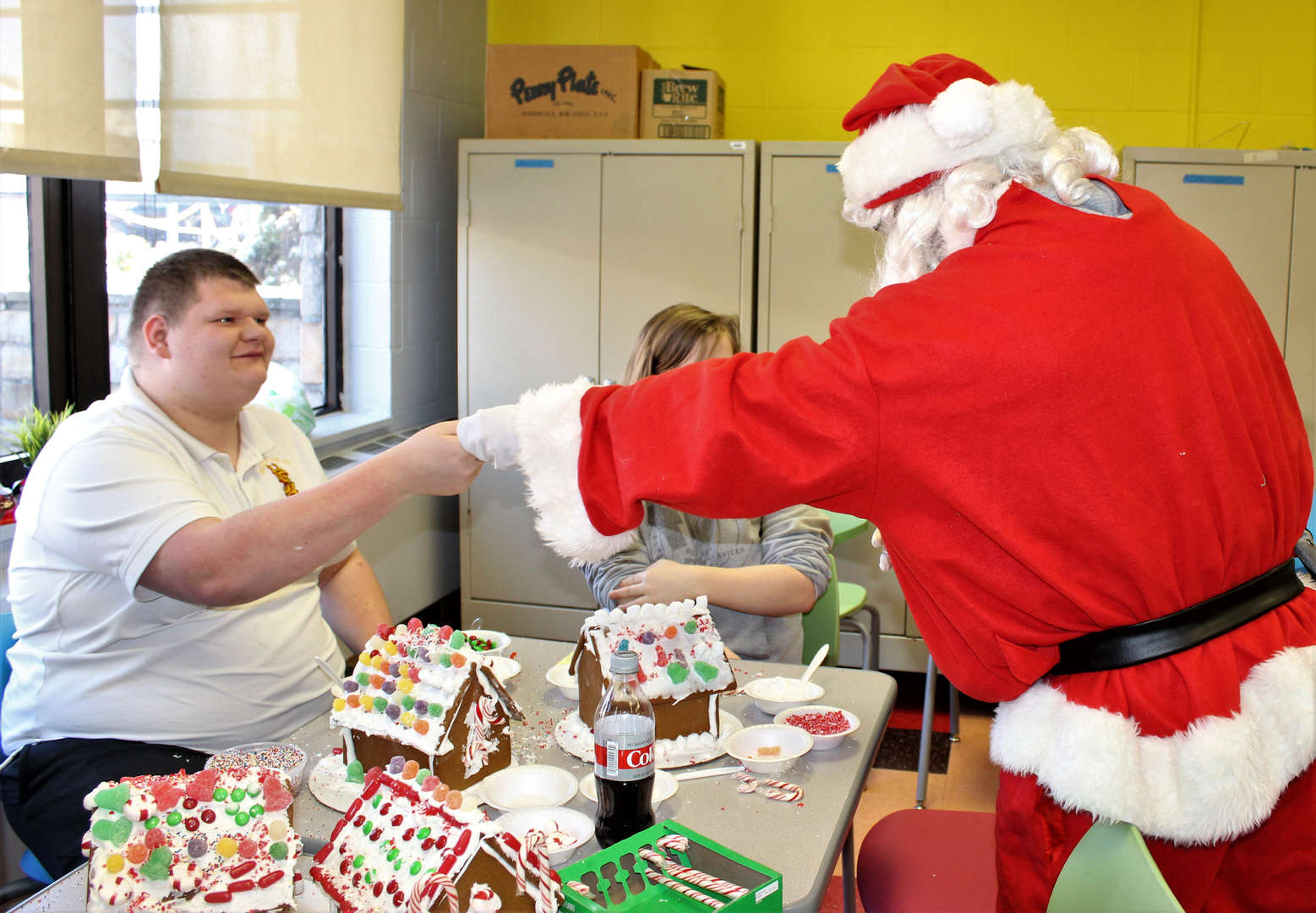 Santa Claus gives a candy cane to a male student during a holiday party.