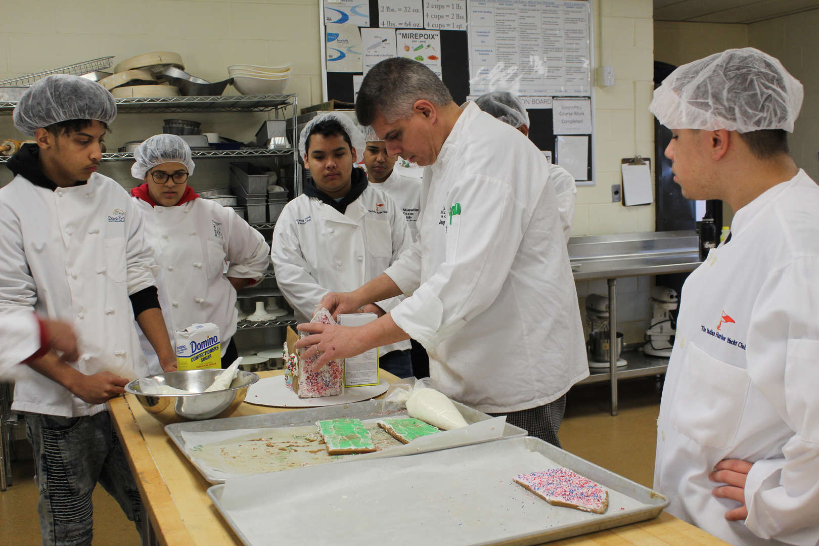 Teacher instructs students on constructing gingerbread houses