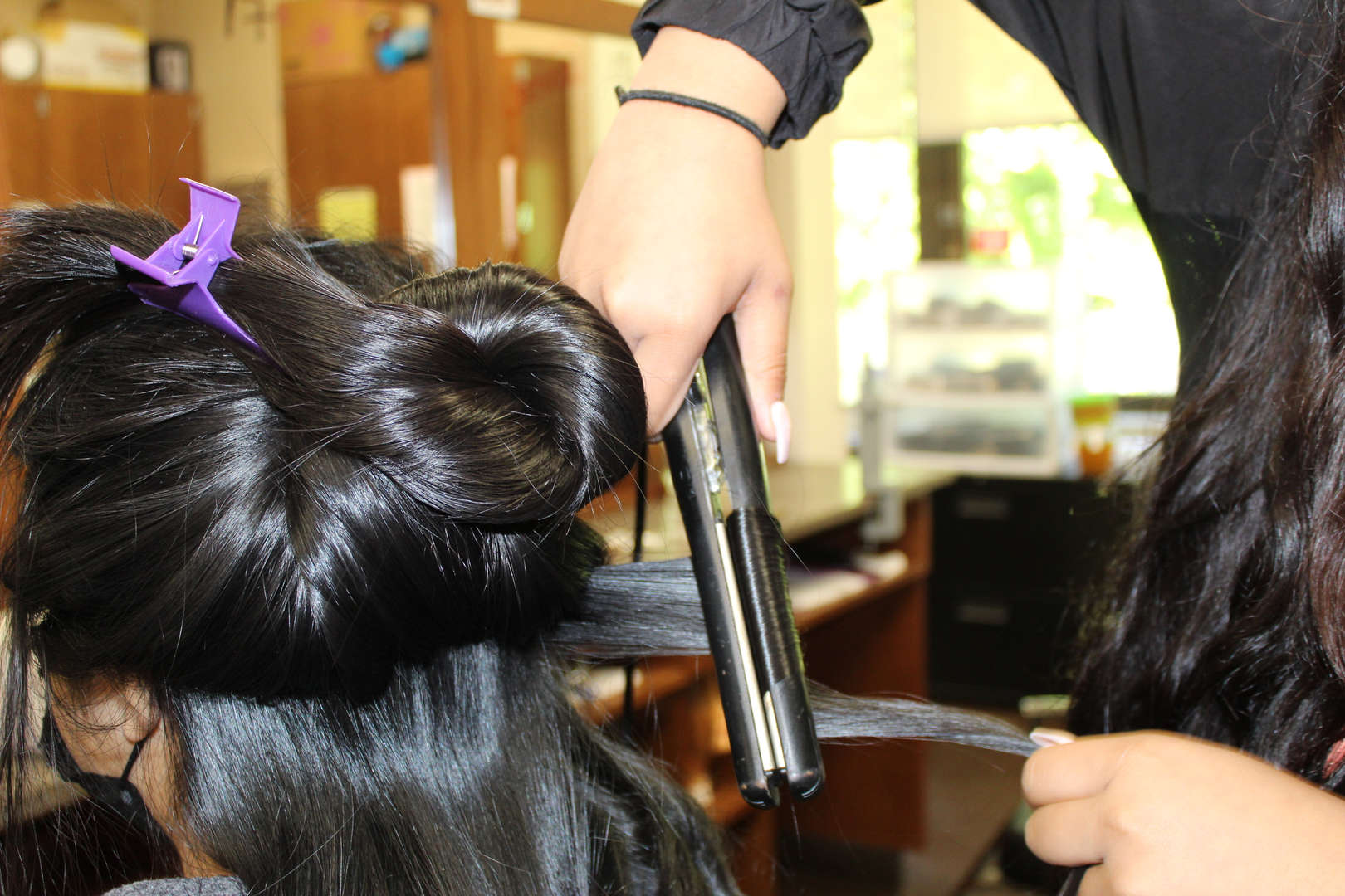 Close up of hair beign curled using a curling iron